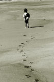 Footprints. A young girl walking down the beach royalty free stock photography