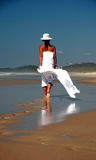 Footprints. Leading to woman in white on beach Stock Image