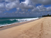 Footprints on the Beach. Summer wave and footprints on the beach of North Shore Stock Photos