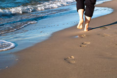 Footprints on the beach. Foot-pure in the sand lead along the water royalty free stock image