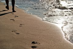 Footprints on the beach. Foot-pure in the sand lead along the water stock photography