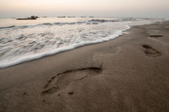 Footprints on a beach. With fisher boats on the horizon near Ngwe Saung in Myanmar Stock Photos