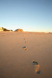 Footprints on the beach. Footprints leading to a distant beachhouse Royalty Free Stock Photos