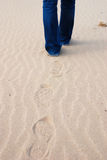Footprints on the beach. Woman walking in the sands Royalty Free Stock Photos