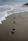 Footprints on the beach. Footprints in the sand along the shore with approaching waves stock photography