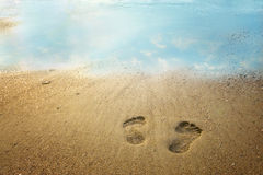 Footprints on the beach. With the sky reflected in the water Royalty Free Stock Image
