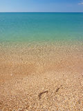 Footprints on the beach and calm sea Stock Photo