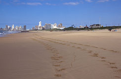Footprints on Beach with City Buildings in Background Stock Photo