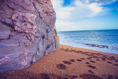 Footprints on the beach by a cliff side Royalty Free Stock Photography