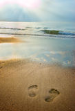 Footprints on the beach at dusk. Footprints on the beach with the sky reflected in the water Stock Photo