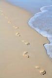 Footprints on beach sand stock image