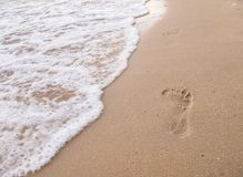 Footprints on the beach with sea waves. Footprints that occurred after someone walked on the beach royalty free stock photography