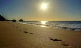 Footprints in a beach. Under a sunset stock photos