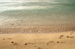 Footprints on beach. Yellow beach with footprints on yellow sand and clear sea Stock Images