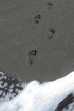 Footprints in Black Sand Royalty Free Stock Images