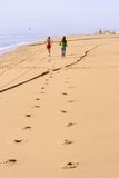 Footprints of competing at the beach. Footprints of a senior man in swimsuit and young woman with casual clothes running at the beach next to the water. The two Royalty Free Stock Photo