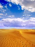 Footprints in desert. Scenic view of Sahara desert under blue sky and cloudscape with footprints receding in foreground Stock Photos
