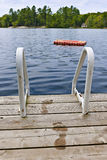 Footprints on dock at summer lake. Wet footprints on dock with ladder and diving platform at lake in Ontario Canada Stock Photos