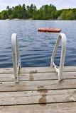 Footprints on dock at summer lake stock photos