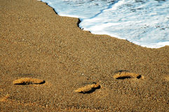 Footprints, gold sand and sea foam Royalty Free Stock Photography