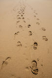 Footprints of hiking boots on the sand of a beach. Royalty Free Stock Image