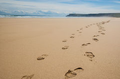 Footprints of hiking boots on the sand of a remote beach Royalty Free Stock Photography