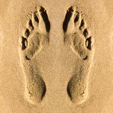 Footprints of human bare feet on the beach sand royalty free stock photography