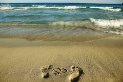 Footprints in love couple in the sand on the beach Stock Photography