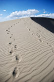 Footprints Over Sand Dunes. Two people and a dog's footsteps over windswept sand dune with cloudy blue sky in background Royalty Free Stock Photos