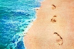Footprints of the people on a golden pink sand on the sea coast. Soft waves of blue and green color. Marine creative background cl Stock Photo