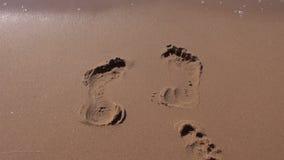 Footprints on resort beach sand and sea waves. Footprints on resort beach sand and sea water waves stock video