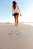 Footprints in sand. Woman walks alone on a deserted beach, solitude, serene, lonely concept. carefree vacation in nature Stock Image