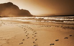 Footprints in the sand on the. Beach. Shot on a sunny day with a mountain in the background royalty free stock photo