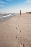 Footprints on sand. Footprints on wet sand in sunset light of one man moving ahead along coastline near the sea Royalty Free Stock Photo