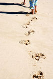 Footprints in sand. Little caucasian bare feet kids walking in the sand on a beach leaving footprints in summertime royalty free stock photo