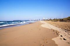 Footprints in Sand Along Durban Beach with city skyline Stock Photos