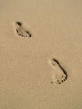 Footprints on sand beach. Two footprints on sand walking towards the camera Royalty Free Stock Photos