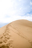 Footprints on sand dune  background of mountains Stock Image