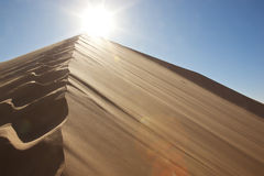 Footprints on sand dune into the sun. Footprints on sand dune in the desert into the sun Royalty Free Stock Photo