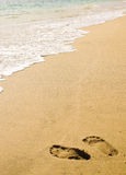 Footprints in the sand in front of coming wave Stock Photos