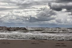 Footprints in the sand and large waves on Lake Michigan Royalty Free Stock Photos