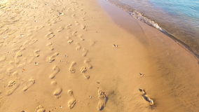 Footprints in the sand, Leave your mark in life. Many human footprints on the sand along the water stock video