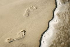 Footprints in sand next to wave. Royalty Free Stock Photo