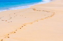 Footprints in the sand by the sea. Footprints on the deserted sandy beach by the sea Royalty Free Stock Image