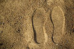 Footprints from shoes on wet sand royalty free stock photos