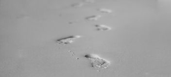 Footprints in the sand at sunset black and white Royalty Free Stock Photos