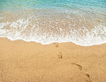 Footprints on sand and turquoise sea water Stock Photos