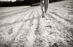 Footprints on the sand with walking girl on background Stock Photo