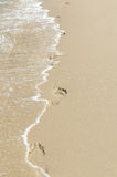 Footprints in the sand. Footprints and wave in the sand Stock Photos