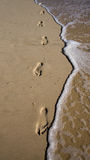 Footprints in the sand with waves Stock Photography